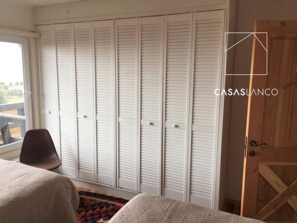 Closets fabricados con puerta de celosía de madera.